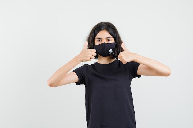 黒のtシャツ、マスクで二重の親指を示し、自信を持って見える少女。正面図。