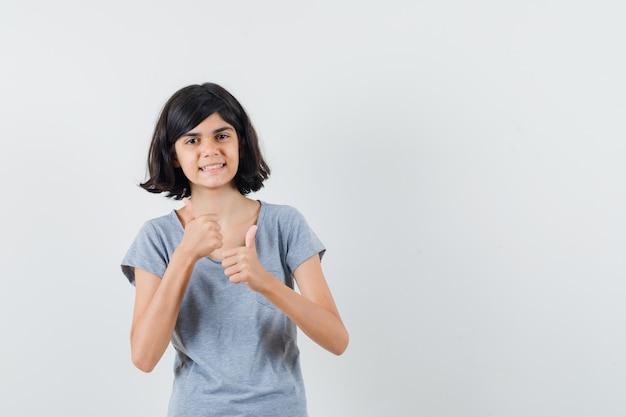 Tシャツを着て二重の親指を見せて陽気に見える少女。正面図。