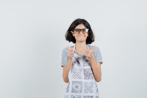 Tシャツで二重親指を示す少女