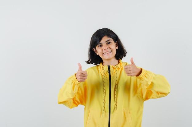 Bambina che mostra i doppi pollici in su in felpa con cappuccio gialla e sembra felice, vista frontale.