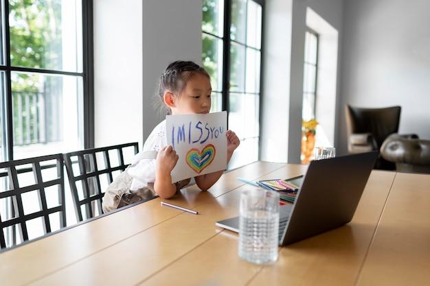 Bambina che mostra un disegno a un membro della sua famiglia durante una videochiamata