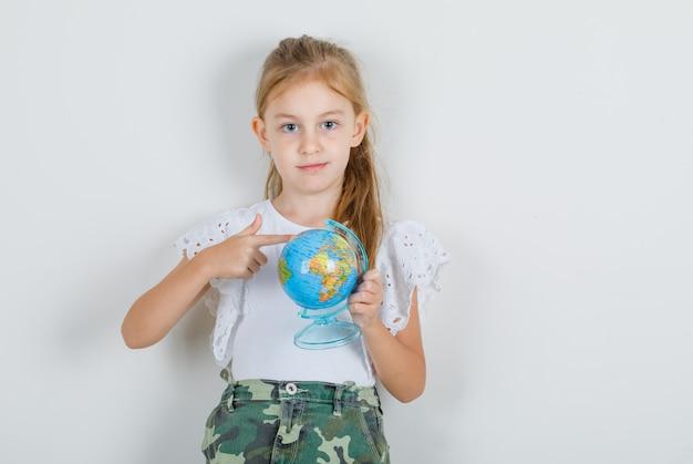 Маленькая девочка показывает глобус пальцем в белой футболке