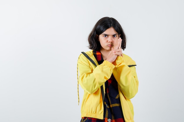 Little girl showing gun gesture in checked shirt, jacket and looking confident , front view.
