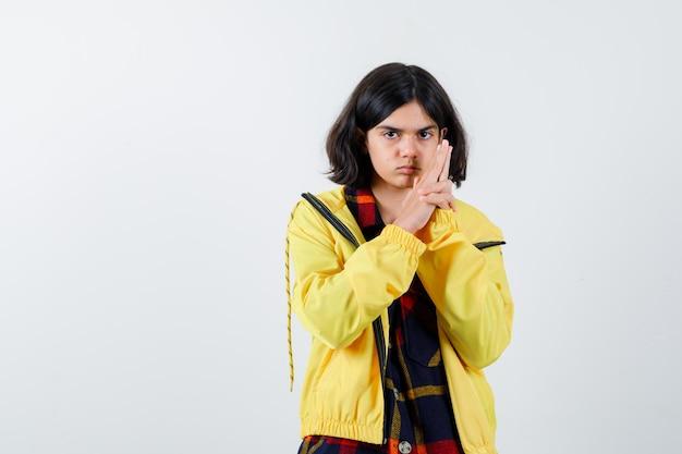Маленькая девочка показывает жест пистолета в проверенной рубашке, куртке и выглядит уверенно, вид спереди.