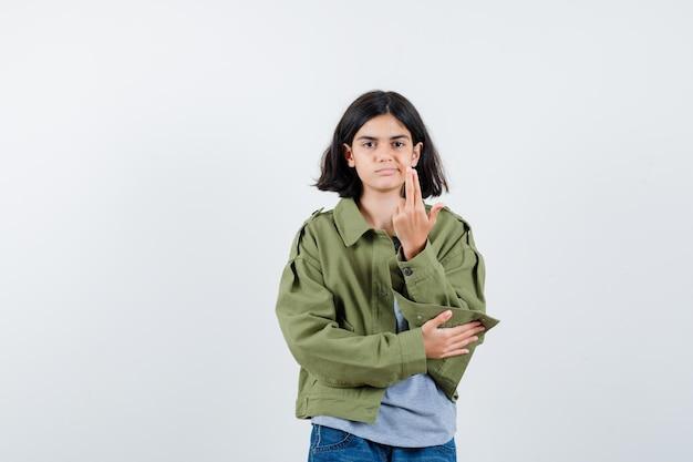 コート、tシャツ、ジーンズで銃のジェスチャーを示し、自信を持って、正面図を探している少女。