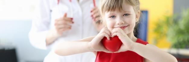 의사 사무실에서 손으로 마음을 보여주는 작은 소녀. 소아 심장학 개념