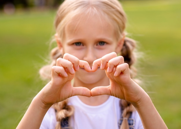 Little girl showing a heart with her fingers