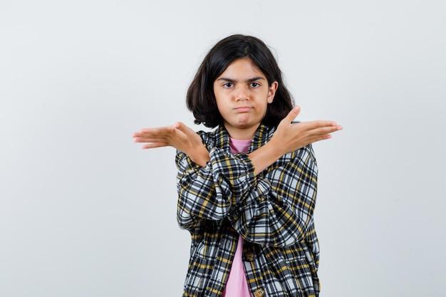 Bambina che mostra gesto impotente con le mani incrociate in camicia, vista frontale della giacca.