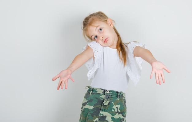 白いtシャツで大胆なジェスチャーを示す少女