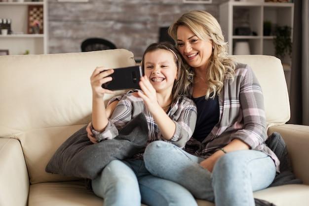 リビングルームのソファに座っている母親と一緒に自分撮りをしながら中かっこを見せている少女。