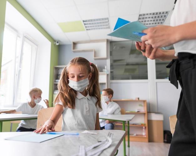 Маленькая девочка показывает свою домашнюю работу учителю