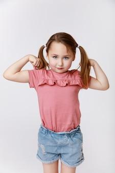 彼女の強さと上腕二頭筋を示している少女は、オリンピックのゲームの準備ができています Premium写真