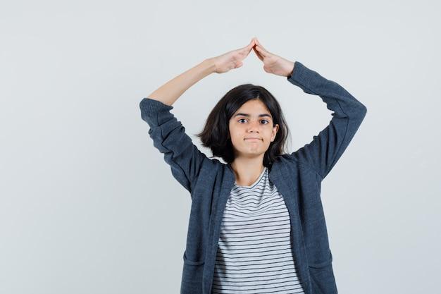 Маленькая девочка показывает жест крыши дома над головой в футболке