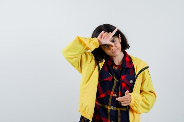Bambina che mostra il gesto del perdente in camicia a quadri, giacca e sguardo malinconico