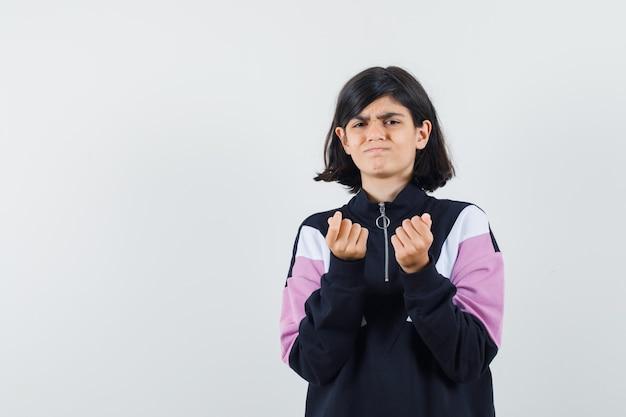 Маленькая девочка показывает жест денег в рубашке и выглядит неимущим. передний план.