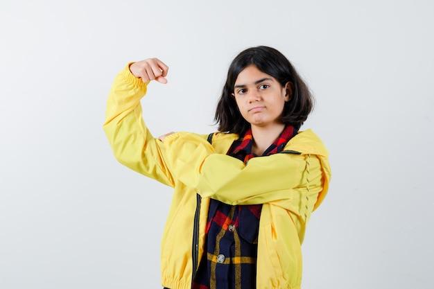 체크 셔츠, 재킷에 팔 근육을 보여주는 어린 소녀와 자신감을 찾고. 전면보기.