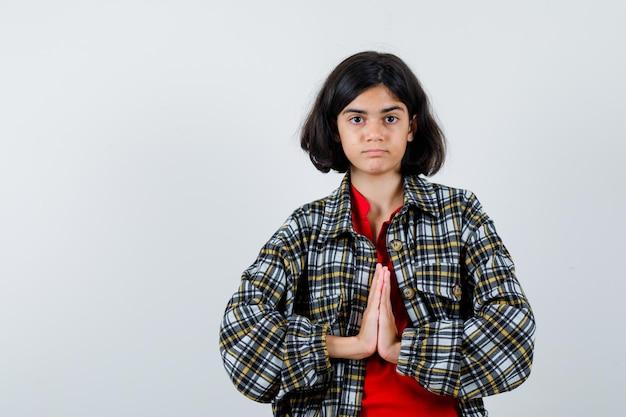 シャツ、ジャケットの正面図でナマステのジェスチャーを示す少女。