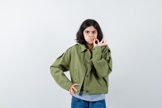 확인 제스처를 보여주는 어린 소녀, 코트, 티셔츠, 청바지에 입술을 구부리고 자신감을 찾고 전면보기.