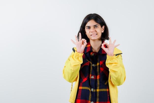 チェックのシャツ、ジャケットで大丈夫なジェスチャーを示し、幸せそうに見える少女。正面図。