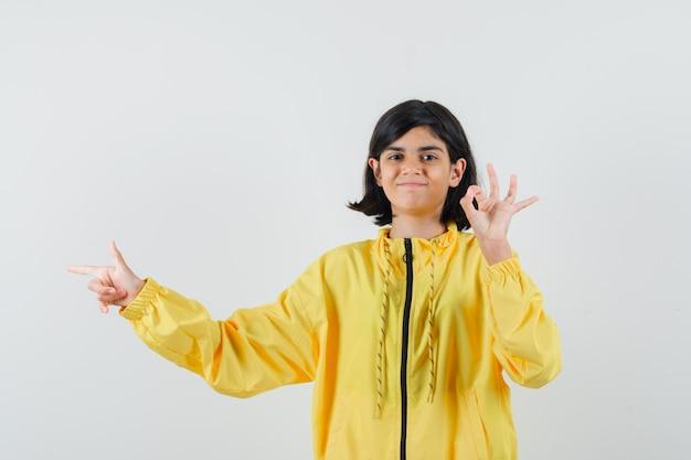 Bambina che mostra il gesto giusto, indicando da parte in felpa con cappuccio gialla e guardando allegra. vista frontale.