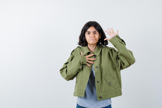 Little girl showing palm while holding hand on chest in coat, t-shirt, jeans and looking confident , front view.