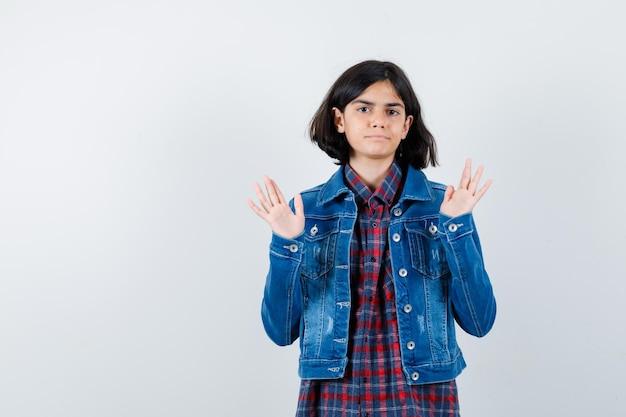 Маленькая девочка показывает ладони в жесте капитуляции в рубашке, куртке и выглядит уверенно. передний план.