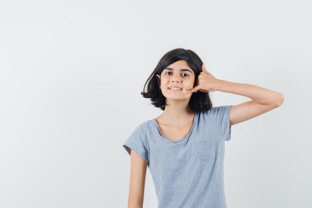 Bambina che mostra il gesto del telefono in maglietta e guardando fiducioso, vista frontale.