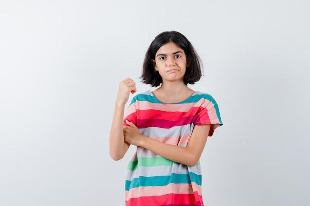 Bambina che mostra gesto di potere in maglietta e sembra dispiaciuta. vista frontale.