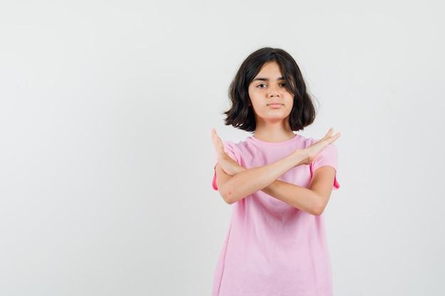 ピンクのtシャツで拒否ジェスチャーを示し、毅然とした表情の少女。正面図。