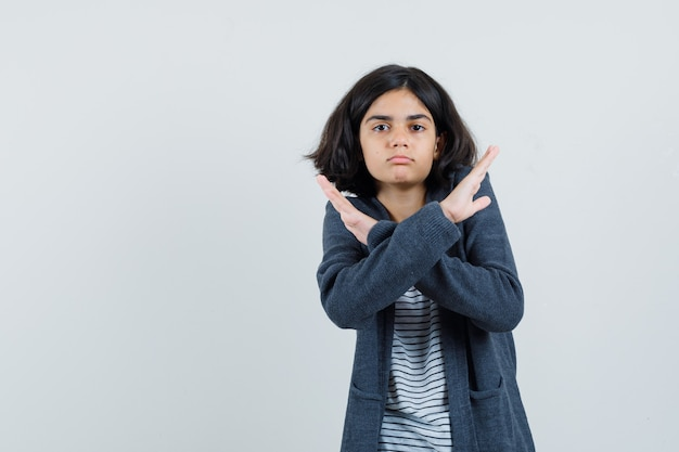 Маленькая девочка показывает жест отказа в футболке, куртке и выглядит измученной.