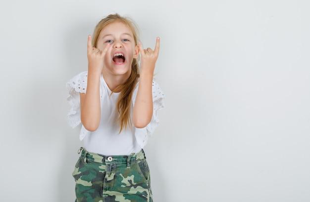 Маленькая девочка показывает знак рок-н-ролла в белой футболке