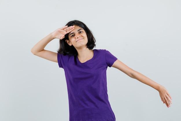 T- 셔츠에 경례 제스처를 보여주는 자랑 스 러 워 보이는 어린 소녀.