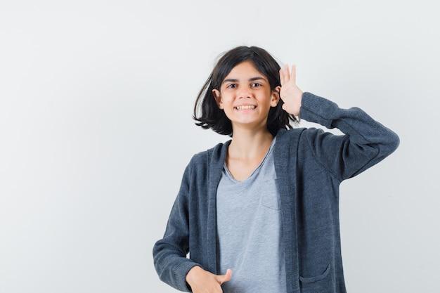 Tシャツ、ジャケット、陽気に見える、正面図で敬礼のジェスチャーを示す少女。