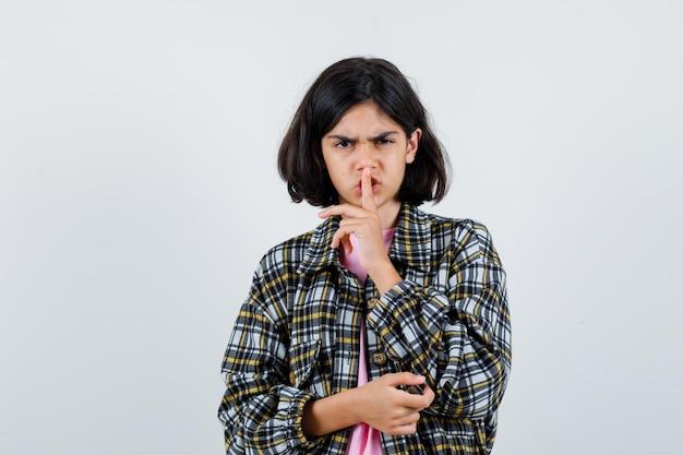 셔츠, 재킷 전면 보기에 침묵 제스처를 보여주는 어린 소녀.