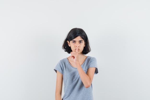 Маленькая девочка показывает жест молчания в футболке и смотрит осторожно, вид спереди.