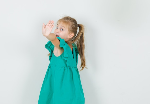 Little girl showing stop gesture in green dress .