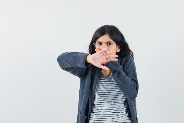 Маленькая девочка показывает жест стоп, держит руку на рту в футболке, куртке и выглядит испуганной.