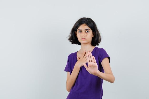 Tシャツで停止ジェスチャーを示し、イライラしているように見える少女。