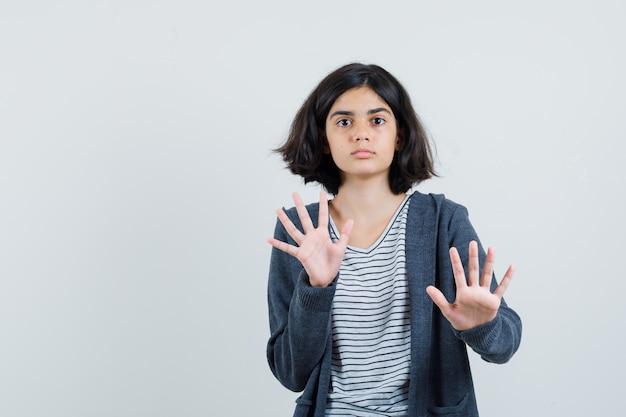 Tシャツ、ジャケットで停止ジェスチャーを示し、おびえているように見える少女