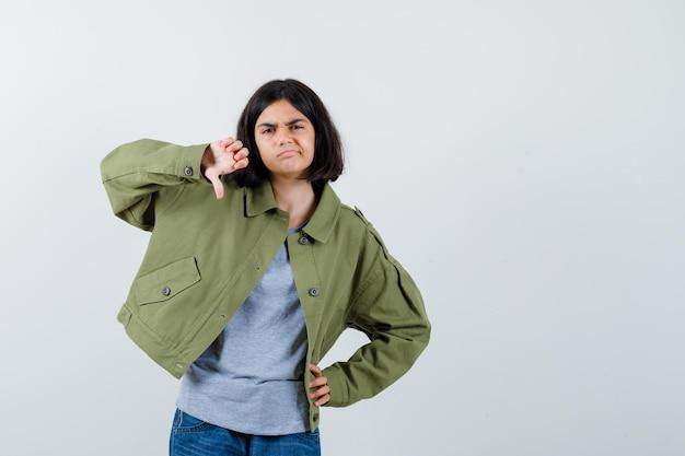 Bambina che mostra pollice giù in cappotto, t-shirt, jeans e sembra insoddisfatta. vista frontale.