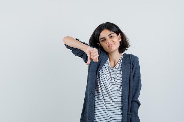 T- 셔츠, 재킷에 아래로 엄지 손가락을 보여주는 불만을보고 어린 소녀