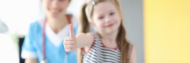 医者の予定のクローズアップで親指を示す少女
