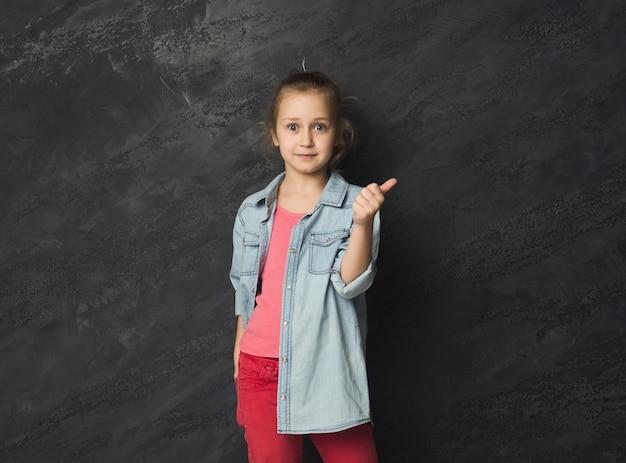 灰色のスタジオの背景に親指を表示している少女。幸せなカジュアルな子供が身振りで示して楽しんでいます。成功と目標達成の概念、コピースペース