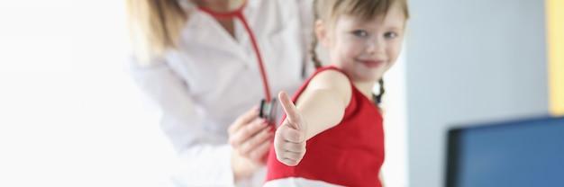 Маленькая девочка показывает палец вверх во время осмотра врачей крупным планом. педиатрическое обследование и лечение детей концепции