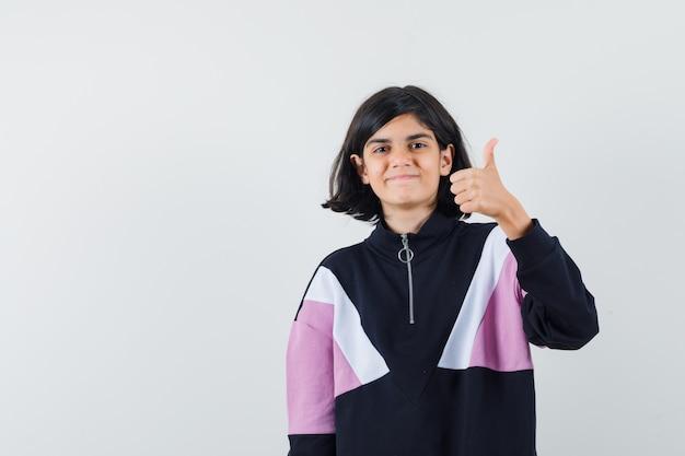 シャツに親指を立てて楽観的に見える少女。正面図。