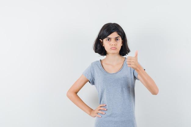 Tシャツに親指を立てて真面目な顔をしている少女、正面図。