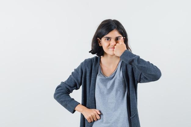 Маленькая девочка показывает палец вверх в футболке, куртке и выглядит счастливой