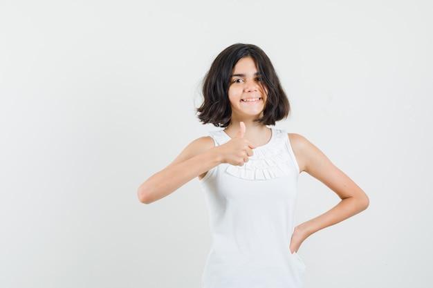 Маленькая девочка показывает палец вверх в белой блузке и выглядит веселым, вид спереди.
