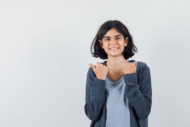 Tシャツ、ジャケットで親指を表示し、幸せそうに見える少女、正面図。