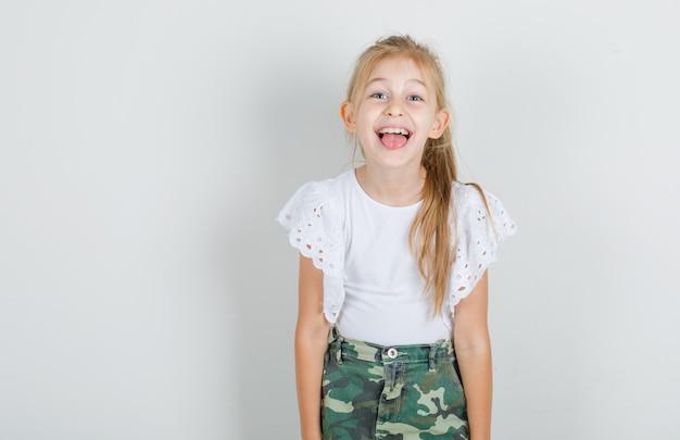 Маленькая девочка показывает язык в белой футболке